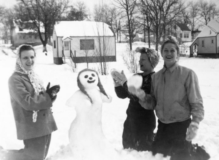 Snowmen Young Women Playing In Snow Building Snowman